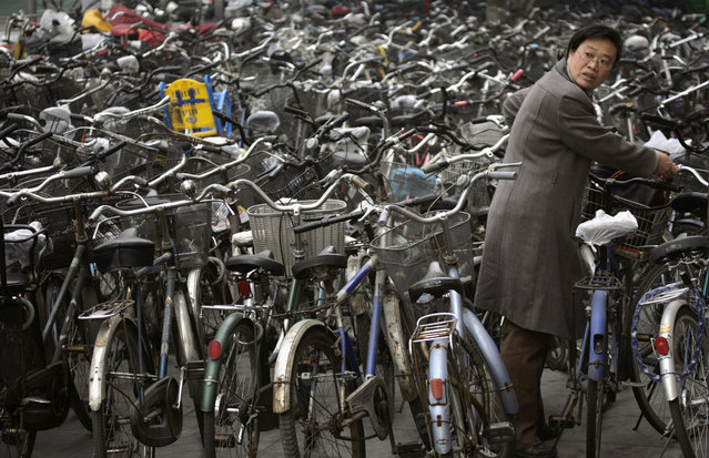 A woman collects her bicycle from a parking lot outside a subway station in Beijing in this November 12, 2007 file photo. (Photo by Reinhard Krause/Reuters)