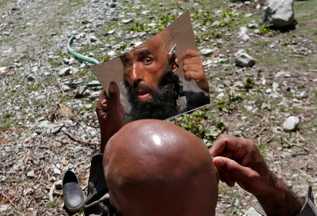 A Bakerwal, or nomadic man, shaves his head alongside a road at Gagangeer in Kashmir's Ganderbal district on September 3, 2020. (Photo by Danish Ismail/Reuters)