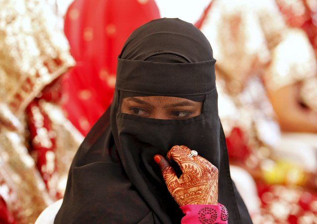 A veiled Muslim bride waits for the start of a mass marriage ceremony in Ahmedabad, India, October 11, 2015. A total of 65 Muslim couples from various parts of Ahmedabad on Sunday took wedding vows during the mass marriage ceremony organised by a Muslim voluntary organisation, organisers said. (Photo by Amit Dave/Reuters)