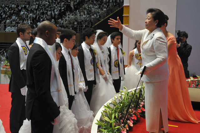 """Hak Ja Han Moon (R), the widow of the late Unification Church founder Sun Myung Moon, sprinkles the church's holy water onto newly-married couples during the church's mass wedding that took place in its headquarters in Gapyeong, east of Seoul, on February 17, 2013.  The Unification Church, set up by Sun Myung Moon in Seoul in 1954, is one of the world's most controversial religious organisations, and its devotees are often dubbed """"Moonies"""" after the founder. (Photo by Kim Jae-Hwan/AFP Photo)"""