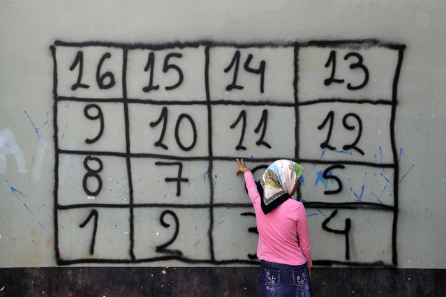 "An Afghan girl counts in Greek the numbers on the wall during a lesson by a non governmental organization at a refugee camp in the western Athens' suburb of Schisto, on Thursday, September 22, 2016. Most of the roughly 60,000 refugees and other migrants stranded in Greece are living in ""appalling conditions"" and face ""immense and avoidable suffering"", rights group Amnesty International said in a report Thursday slamming Europe's response to the refugee crisis. (Photo by Thanassis Stavrakis/AP Photo)"