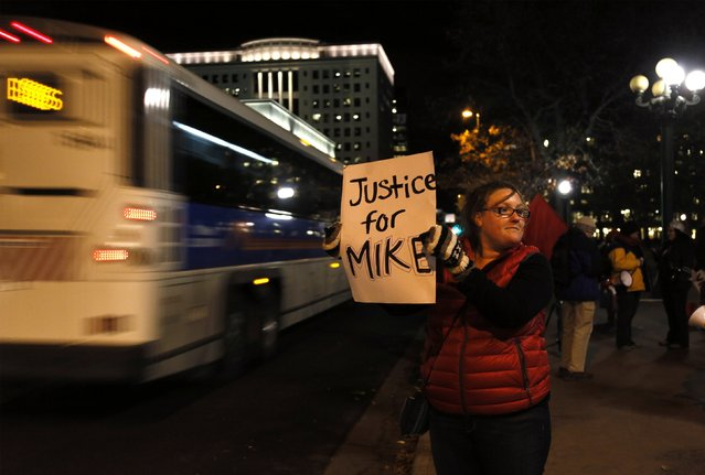 A protester holds a sign in downtown Denver, November 24, 2014 after a grand jury declined to bring murder charges against a Ferguson, Missouri police officer who killed unarmed teenager Michael Brown. White Missouri police officer Darren Wilson will not be charged for fatally shooting the unarmed black teenager in August, authorities said on Monday, after a killing that sparked angry protests in a St. Louis suburb and outrage over police treatment of minorities. (Photo by Rick Wilking/Reuters)