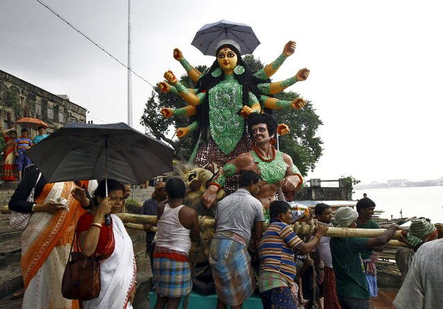 The idol of Hindu goddess Durga is being loaded onto a boat to transport it through the waters of river Ganga to a pandal or a temporary platform ahead of the Durga Puja festival in Kolkata, India, October 15, 2015. (Photo by Rupak De Chowdhuri/Reuters)