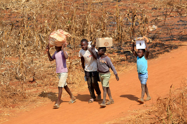 Children walk on a dusty road carrying items in Harare, Zimbabwe, 24 September 2020. At the end of March 2020, a total of 9,500 schools were closed due to the COVID-19 pandemic. According to UNICEF, a third of the world's school children are unable to access online learning during school closures. (Photo by Aaron Ufumeli/EPA/EFE/Rex Features/Shutterstock)