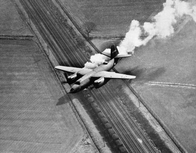 This Marauder medium bomber is not in distress. The white smoke is coming from a locomotive on the tracks below and not from the right engine of the plane. Flying over the English countryside while returning from a raid over Europe, February 17, 1944. (Photo by AP Photo)