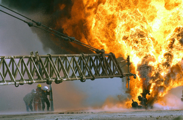 Kuwaiti firefighters secure a burning oil well in the Rumaila oilfields, on March 27, 2003, set ablaze by Iraqi military forces. (Photo by Mary Rose Xenikakis/USMC/The Atlantic)