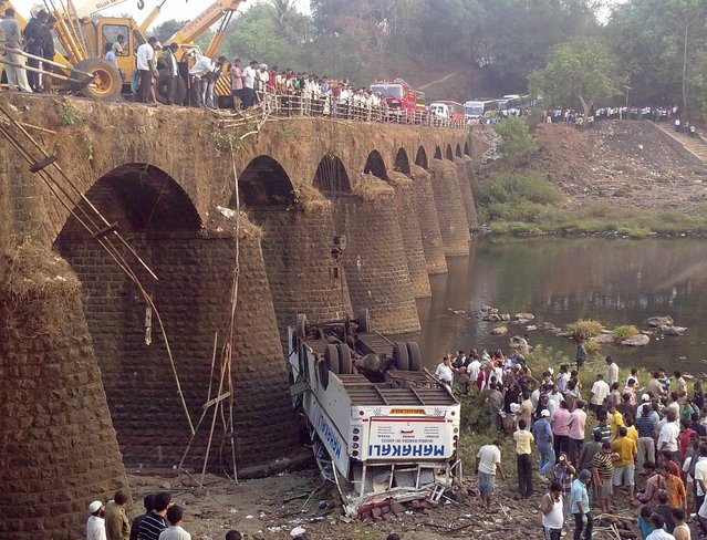 Rescuers and bystanders look at the wreckage of a passenger bus after it fell from a bridge in Ratnagiri district in the western Indian state of Maharashtra March 19, 2013. At least 37 people were killed and 15 others injured after the bus fell into the Jagbudi River in Ratnagiri district on Tuesday morning, local media reported. (Photo by Reuters/Stringer)