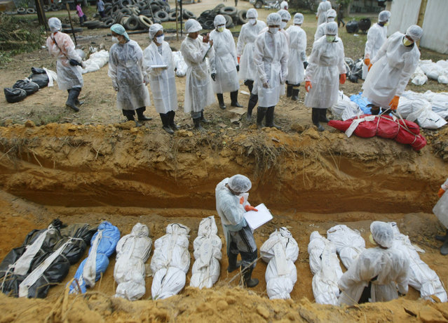 Thai health officials bury tsunami victims in masses at a burial site in Takuapa, north of the Thai resort island of Phuket, in this January 1, 2005 file photo. (Photo by Chaiwat Subprasom/Reuters)