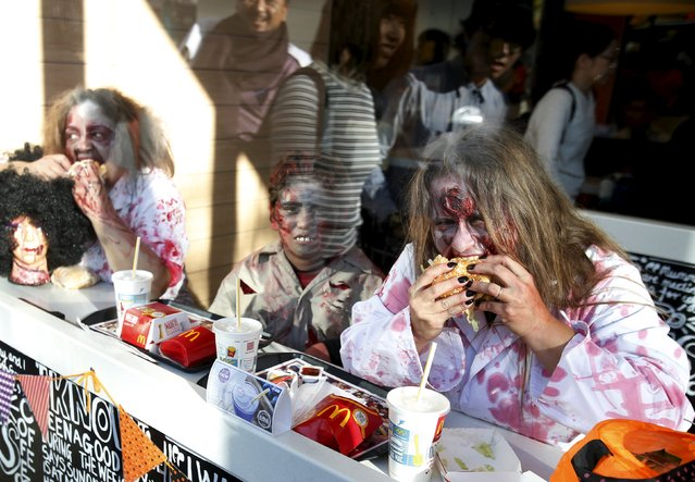Participants in costume eat hamburgers inside a fast food restaurant after a Halloween parade in Kawasaki, south of Tokyo, October 25, 2015. (Photo by Yuya Shino/Reuters)