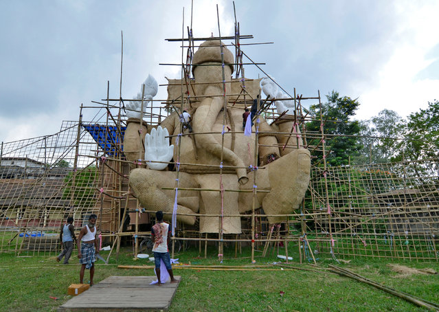 Artisans work on a giant model of Hindu god Ganesh, the deity of prosperity, during preparations for the upcoming Durga Puja festival in Nagaon district, Assam, September 30, 2016. (Photo by Anuwar Hazarika/Reuters)