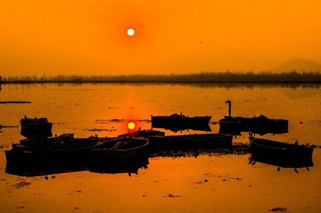 "Boats moored in the middle of Dal lake are silhouetted against the setting sun on January 15, 2018 in Srinagar, the summer capital of Indian administered Kashmir, India. Kashmir, the Muslim majority state, known as the ""Paradise on Earth"" has for centuries captured the imagination of many writers, poets and film makers and is integral to the tourist trade. Kashmir has been a contested land between nuclear neighbors India and Pakistan since 1947, the year both the countries attained freedom from the British rule. (Photo by Yawar Nazir/Getty Images)"