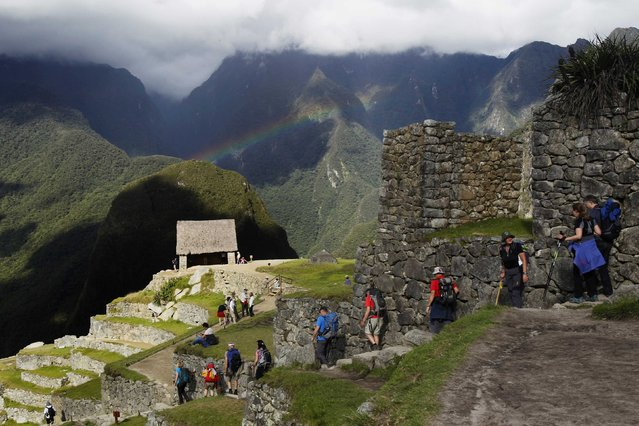 Visitors view a rainbow at the Inca citadel of Machu Picchu in Cusco December 2, 2014. (Photo by Enrique Castro-Mendivil/Reuters)