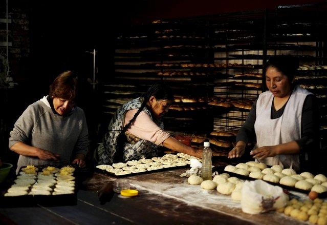 Women prepare bread in a backhouse in La Paz, October 28, 2015. (Photo by David Mercado/Reuters)