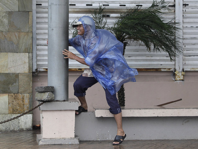 A man holds on to a pole as strong winds blow brought by Typhoon Hagupit in Legazpi, Albay province, eastern Philippines on Sunday, December 7, 2014. (Photo by Aaron Favila/AP Photo)
