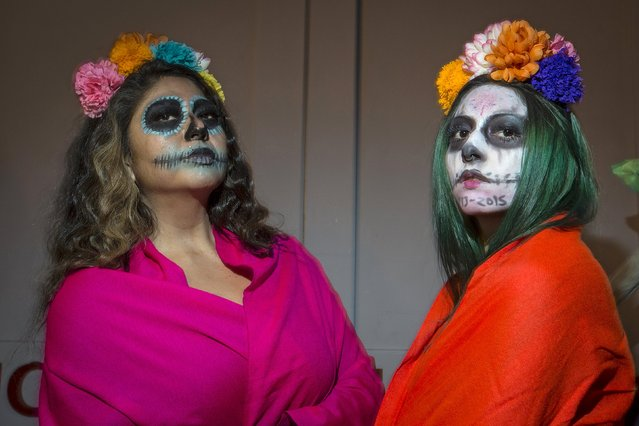 "Women dressed in a ""Dia de Muertos"" or ""Day of the Dead"" theme pose for a photo as they wait in line to participate in the Greenwich Village Halloween Parade in the Manhattan borough of New York, October 31, 2015. (Photo by Carlo Allegri/Reuters)"