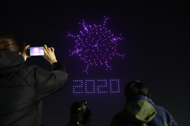 Drones fly over the Olympic Park make the shape of coronavirus to send messages to support the country and share measures to contain the spread of the coronavirus (COVID-19) on November 13, 2020 in Seoul, South Korea. South Korea's new coronavirus cases spiked to almost 200 Friday, the highest in 70 days, as sporadic cluster infections from informal gatherings continued to pop up across the nation, forcing health authorities to consider raising the social distancing scheme. (Photo by Chung Sung-Jun/Getty Images)