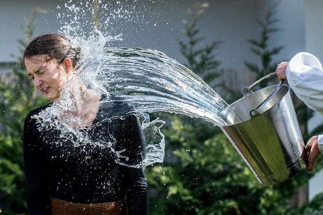 Members of the Mayossa folk dance group pour water on a young woman in Kiskunmajsa, Hungary on April 2, 2018. According to an old Hungarian tradition, celebrated for several hundred years, young men pour water on young women, who in exchange present their sprinklers with beautifully colored eggs on Easter Monday. (Photo by Sandor Ujvari/EPA/EFE/Rex Features/Shutterstock)