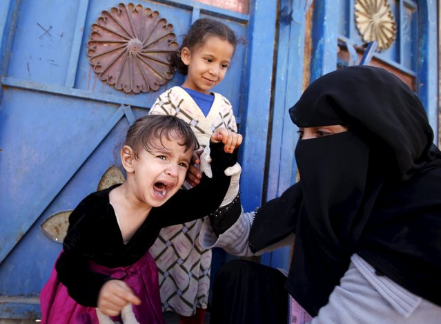 A girl reacts as she receives polio vaccine drops during a house-to-house vaccination campaign in Yemen's capital Sanaa, November 10, 2015. (Photo by Khaled Abdullah/Reuters)
