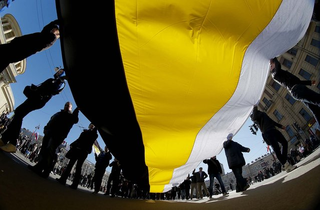Russian nationalists carry a giant Russian Imperial flag during a May Day rally in St. Petersburg. (Photo by Dmitry Lovetsky/Associated Press)