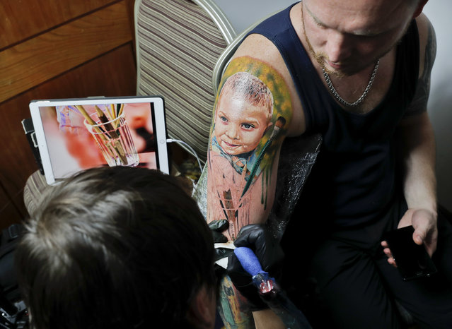 Serghei, from the Republic of Moldova, gets a tattoo showing his son Chiril applied to his hand, during the International Tattoo Convention Bucharest 2016 in Bucharest, Romania, Sunday, October 16, 2016. (Photo by Vadim Ghirda/AP Photo)