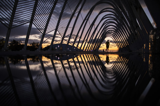 A man runs on a walkway of steel vaults, called the Agora, at the Athens Olympic Stadium complex as the sun sets, on Friday, November 20, 2020. The government imposed a second lockdown nationwide on Nov. 7, expanding regional restrictions, following a dramatic surge in COVID-19 cases (Photo by Petros Giannakouris/AP Photo)