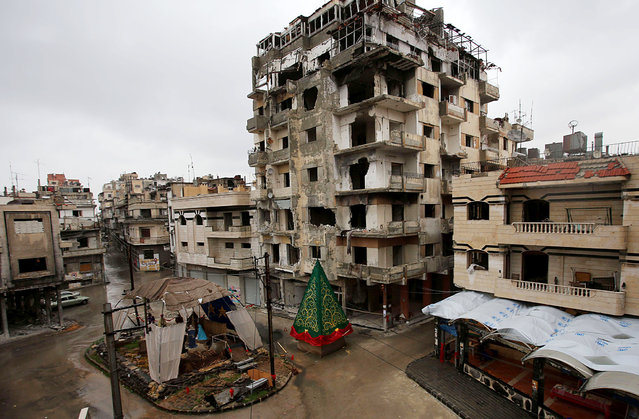 A crib made out of rubble and a Christmas tree are set on a roundabout in the regime-held Hamedieh neighborhood in the Syrian city of Homs on December 22, 2014, as Christians around the world prepare to celebrate the holy day. (Photo by Youssef Karwashan/AFP Photo)