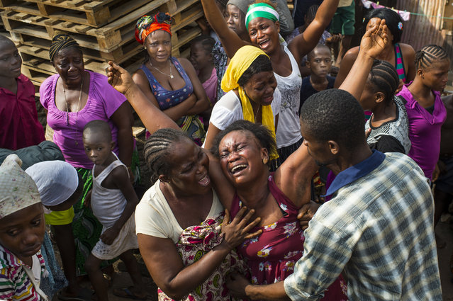 Family members mourn the death of 12-year-old Isata Kallon in Freetown, Sierra Leone, as Ebola cases continue to rise on Sunday, November 23, 2014. Swabs are taken from the deceased to test for Ebola and all burials in Sierra Leone adhere to strict rules to prevent the spread of the disease. (Photo by Nikki Kahn/The Washington Post)