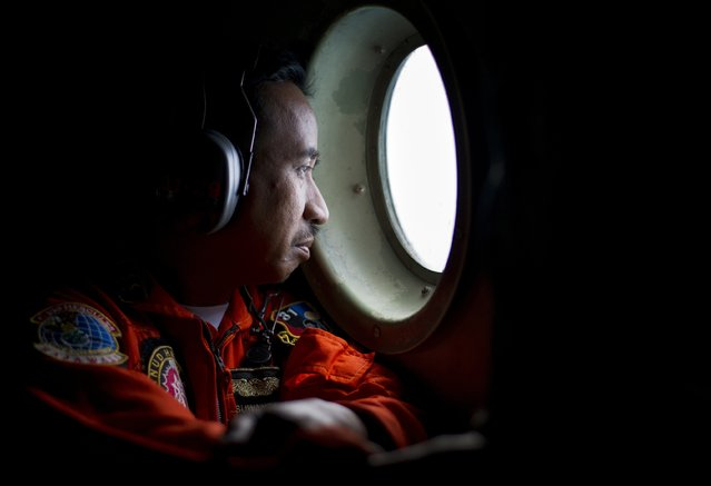 A member of an Indonesian Hercules C130 aircrew watches through a window while monitoring the Belitung Timur sea during search operations for AirAsia flight QZ8501 near Belitung island, December 29, 2014 in this photo taken by Antara Foto. (Photo by Wahyu Putro/Reuters/Antara Foto)