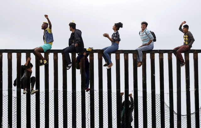 Central American migrants sit on top of the border wall on the beach in San Diego during a gathering of migrants living on both sides of the border, Sunday, April 29, 2018. (Photo by Chris Carlson/AP Photo)