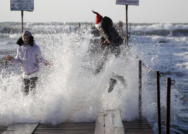 Youths play in a wave crashing on a sea wall in the Russian Black Sea coastal town of Anapa December 28, 2014. (Photo by Eduard Korniyenko/Reuters)