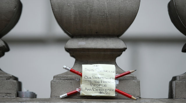 A tribute to the people killed at Paris offices of weekly newspaper Charlie Hebdo, is fixed to the wall outside the French Embassy in London, Thursday, January 8, 2015.  Masked gunmen stormed the Paris offices of a weekly newspaper that caricatured the Prophet Muhammad, methodically killing 12 people at the offices of the Charlie Hebdo, Wednesday, including the editor, before escaping in a car. It was France's deadliest postwar terrorist attack. (Photo by Alastair Grant/AP Photo)