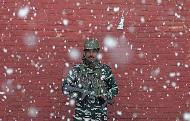 An Indian Paramilitary soldier stands guard during snowfall in Srinagar, the summer capital of Indian Kashmir, 05 January 2021. Kashmir continues to witness medium to the heavy snowfall across all the areas for the third consecutive day, while traffic on the 300-kilometer long Srinagar-Jammu highway continues to be halted for the third day, the air traffic has also remained disturbed for the last two days with the majority of flights getting cancelled. The weather department has issued a weather advisory to hilly areas that is prone to avalanches. The department has also predicted moderate to heavy snowfall for next two days. (Photo by Farooq Khan/EPA/EFE)