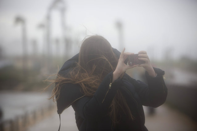 An Israeli girl takes photos of high waves in the Mediterranean Sea with her mobile phone in Tel Aviv, Israel, Wednesday, January 7, 2015 during a heavy winter storm seeping through the Middle East. (Photo by Oded Balilty/AP Photo)