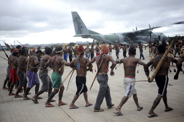 Munduruku Indians do a dance around a Brazilian Air Force plane that transported them to Brasilia for talks with the government, in Brasilia June 4, 2013. Air Force planes flew 144 Munduruku Indians to Brasilia for talks to end a week-long occupation of the controversial Belo Monte dam on the Xingu River, a huge project aimed at feeding Brazil's fast-growing demand for electricity. (Photo by Ueslei Marcelino/Reuters)
