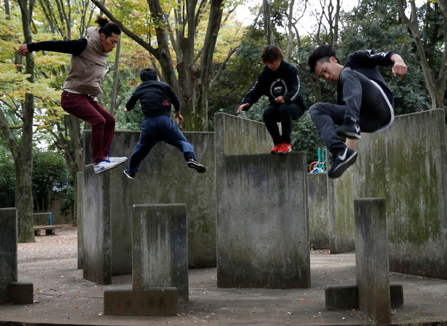 Jun Sato (2nd L), founder of Japan's first parkour educational institute SENDAI X-TRAIN, demonstrates his parkour skill with other practitionners  at a park in Tokyo, Japan November 2, 2016. (Photo by Kim Kyung-Hoon/Reuters)