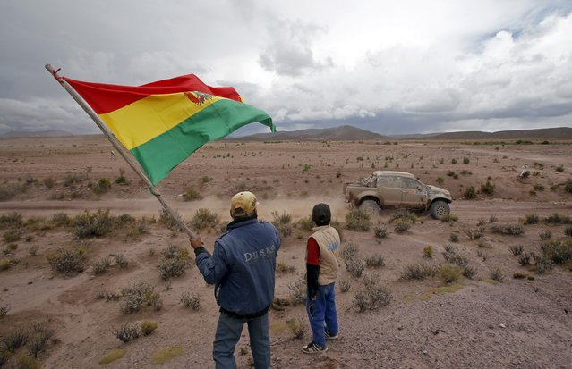 A competitor of the Dakar Rally is cheered by spectators during the 7th stage of the Dakar Rally 2015, from Iquique to Uyuni January 10, 2015. (Photo by Jean-Paul Pelissier/Reuters)