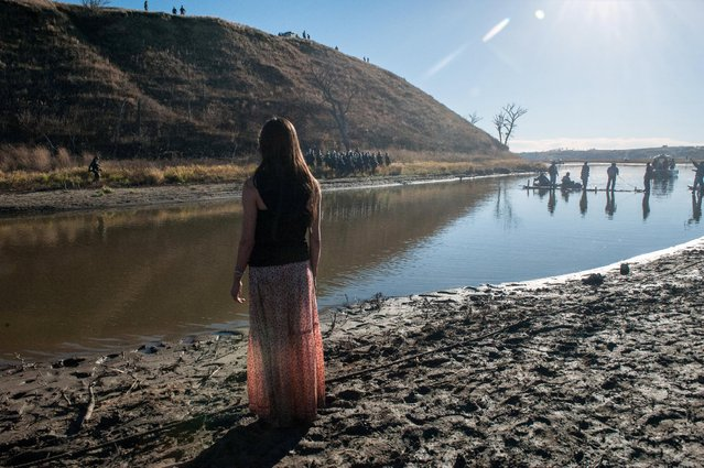 A woman prays at the edge of a river during a protest against the building of a pipeline near the Standing Rock Indian Reservation near Cannonball, North Dakota, U.S. November 2, 2016. (Photo by Stephanie Keith/Reuters)