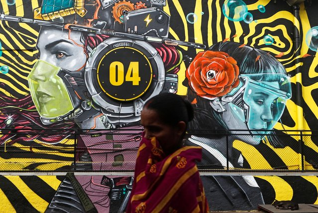 A woman walks past a graffiti of people wearing protective masks amidst the spread of the coronavirus disease (COVID-19), on the outskirts of Mumbai, India, December 9, 2020. (Photo by Francis Mascarenhas/Reuters)