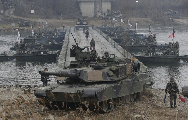 U.S. M1A2 SEP Abrams battle tanks cross the Hantan river during a river crossing operation, part of an annual joint military exercise between South Korea and the United States against a possible attack from North Korea, in Yeoncheon, south of the demilitarized zone that divides the two Koreas, South Korea, Thursday, December 10, 2015. It was the last day of the exercise by the two allies that began on Dec. 1. (Photo by Ahn Young-joon/AP Photo)