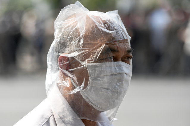 A man wearing a plastic bag as precaution against the coronavirus disease (COVID-19), takes part in protests demanding to reduce the Royal budget and distribute it to people, in front of the government house in Bangkok, Thailand on January 26, 2021. (Photo by Challinee Thirasupa/Reuters)