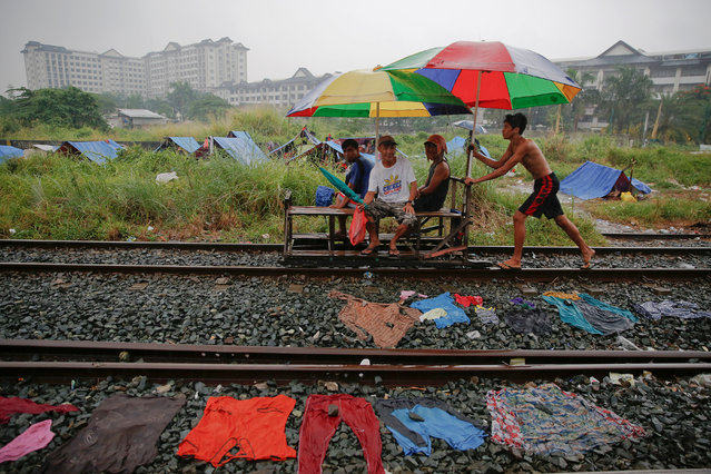 A man pushes passengers on a makeshift trolley in an area where, according to local residents, several people have been killed in police operations since the beginning of country's war on drugs, in Manila, Philippines November 2, 2016. (Photo by Damir Sagolj/Reuters)