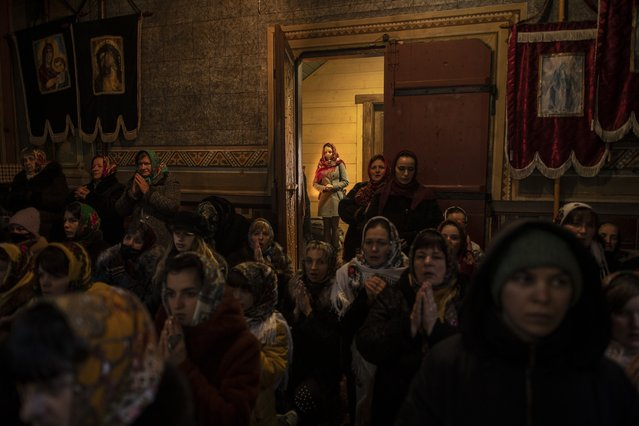 Parishioners attend the Orthodox Christmas Mass in the Holy Trinity church in Iltsi village, Ivano-Frankivsk region of Western Ukraine, Thursday, January 7, 2021. Although Ukraine is struggling to contain the coronavirus pandemic that has inundated its overburdened medical system with patients, Orthodox Christmas celebrations on Thursday occurred widely without masks or social distancing. (Photo by Evgeniy Maloletka/AP Photo)