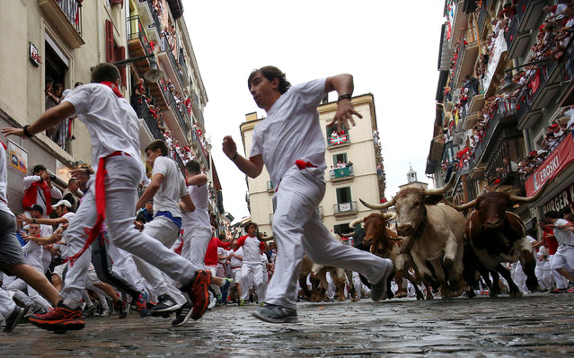 Runners sprint in front of wild cows during the first running of the bulls of the San Fermin festival in Pamplona, Spain, July 7, 2018. (Photo by Susana Vera/Reuters)