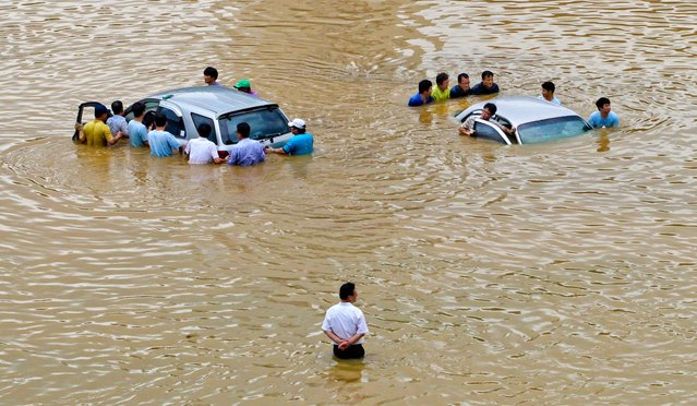 People push cars out of flood waters in Seoul, South Korea, on July 22, 2013. Heavy rains battered the central part of the Korean Peninsula, flooding homes and roads. (Photo by Ahn Young-joon/Associated Press)