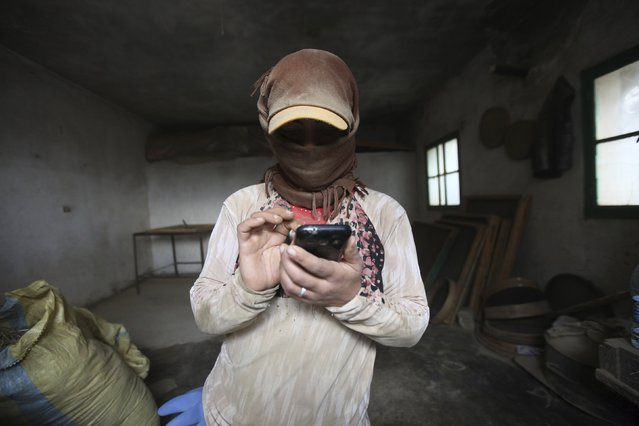 A 29-year-old woman (who asked to withhold her name) is covered in cannabis dust while talking to her family in Raqqa on her mobile phone inside a garage in the Bekaa valley, Lebanon November 1, 2015. (Photo by Alia Haju/Reuters)