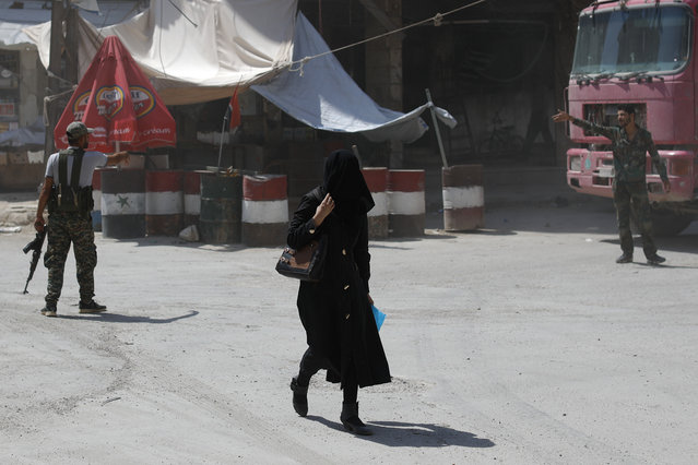 In this Sunday, July 15, 2018, photo, a Syrian woman passes by an Army check point, in the town of Douma in the eastern Ghouta region, near the Syrian capital Damascus, Syria. The celebratory mood in government-controlled areas stems from successive military advances in the past year and an impression that President Bashar Assad, with massive support by unwavering allies Russia and Iran, has won the war or at least militarily defeated the opposition trying to topple him. (Photo by Hassan Ammar/AP Photo)