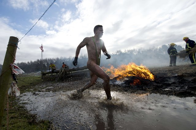 """A competitor take part in the """"Tough Guy"""" adventure race near Wolverhampton, Staffordshire, West Midlands, on February 1, 2015. The event challenges thousands of competitors to run through a gruelling 200 obstacles including water, fire, and tunnels after a lengthy run at the start. (Photo by Oli Scarff/AFP Photo)"""