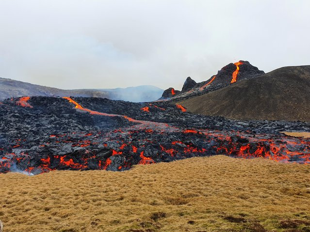 Lava flows from a volcano in the Reykjanes Peninsula, Iceland March 20, 2021. The volcano erupted near Iceland's capital Reykjavik on Friday, shooting lava high into the night sky after thousands of small earthquakes in recent weeks. (Photo by  Icelandic Coast Guard via Reuters)