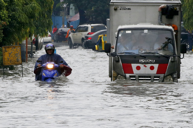 Vehicles negotiate a flooded street in Manila after overnight Southwest monsoon rains brought about by tropical storm Ampil inundated low-lying areas in Metropolitan Manila and nearby provinces Friday, July 20, 2018 in Manila, Philippines. (Photo by Bullit Marquez/AP Photo)