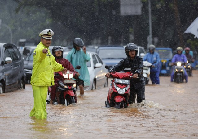 A policeman directs traffic on a flooded street outside the Presidential Palace, after heavy seasonal rains flooded parts of Jakarta February 9, 2015. (Photo by Darren Whiteside/Reuters)
